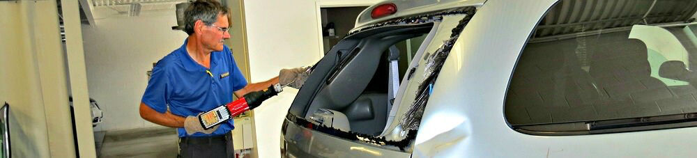 installer working on rear windshield of silver vehicle