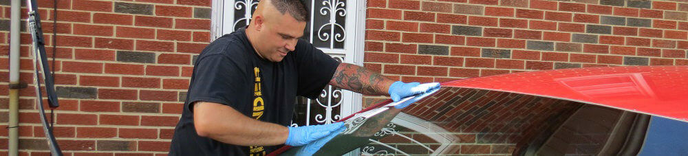 Installer putting finishing touches on replacement windshield