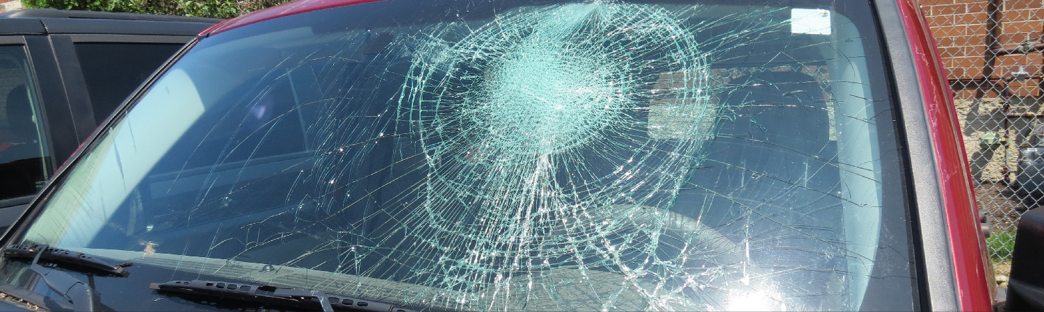 up close image of shattered windshield on red truck
